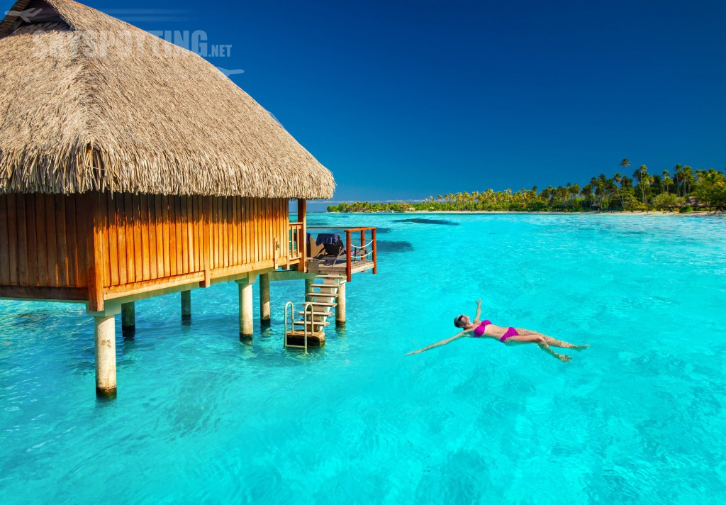 39174827 - woman swimming in tropical lagoon next to overwater villa